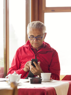Senior man sitting in a coffee shop using cell phone - LAF01771