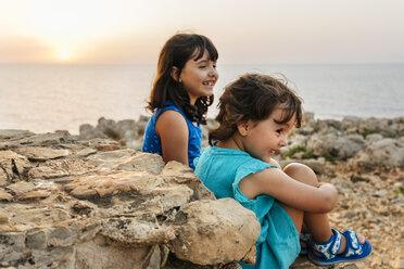 Two happy little girls enjoying sunset near the sea - MGOF02569