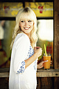 Portrait of smiling blond woman with beverage standing in front of a beach hut - GDF01163