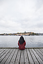 Sweden, Stockholm, back view of woman sitting on pier looking to the city - ABZF01439