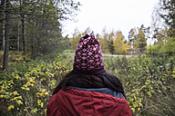 Back view of woman wearing patterned wooly hat in nature - ABZF01445