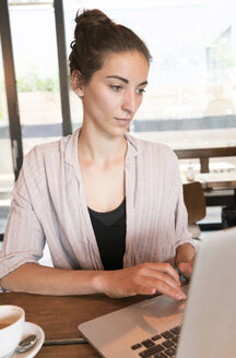 Young woman working with laptop in a coffee shop - TAMF00732