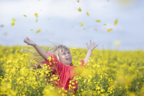 Happy little girl standing in rape field throwing blossoms in the air - ZEF11125