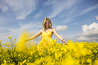 Happy blond woman wearing yellow dress standing in rape field - ZEF11131