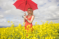 Blond young woman wearing red dress standing in rape field holding red umbrella - ZEF11137