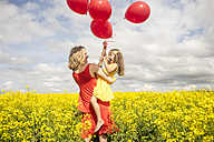 Mother and little daughter having fun with red balloons in rape field - ZEF11140
