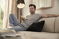 Relaxed man at home sitting on couch with cell phone - SUF00088