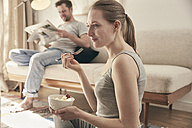 Woman eating fruits in living room with man in background - SUF00091