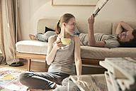 Woman drinking tea in living room with man lying on couch with newspaper - SUF00094