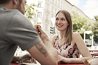 Smiling woman looking at man at a sidewalk cafe - SUF00100