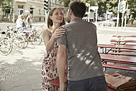 Man and woman meeting at a sidewalk cafe - SUF00106