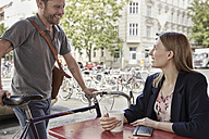 Smiling man with bicycle arriving at a sidewalk cafe looking at woman - SUF00109