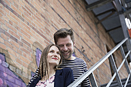 Smiling couple on stairs outdoors - SUF00112