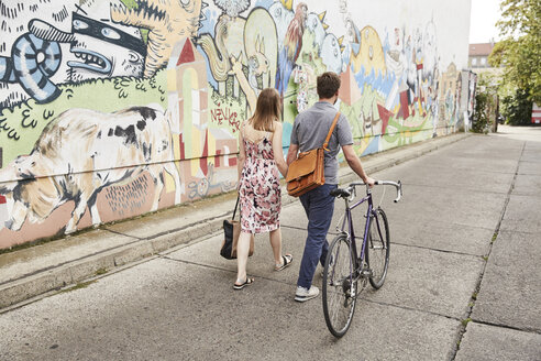 Couple with bicycle passing wall with graffiti - SU00118