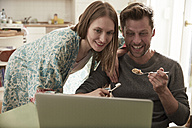 Happy couple looking at laptop together - SUF00136
