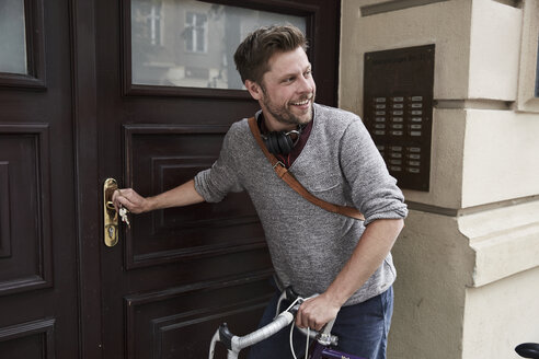Man with bicycle at front door - SUF00139