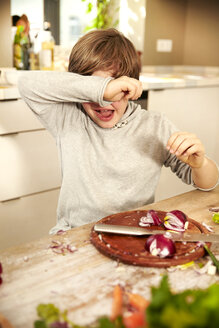 Boy chopping onions covering his eyes - TSFF00134
