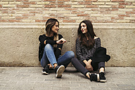 Two best friends sitting in front of facade talking together - EBSF01855