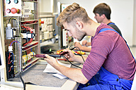 Two electrician students working at electrical panel - LYF00614