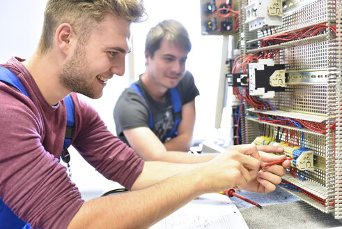 Two electrician students working at electrical panel - LYF00617
