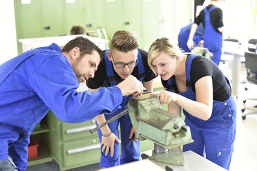 Instructor with trainees at workbench - LYF00623