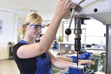 Female trainee working at press drill - LYF00629