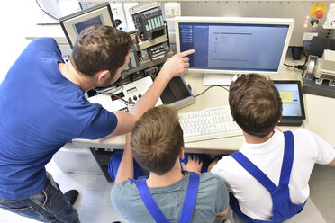 Technical instructor teaching students at computer screen - LYF00635