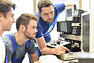 Technical instructor teaching students at computer screen - LYF00638