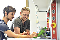 Smiling technical students looking at device - LYF00656