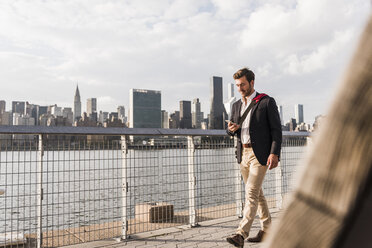 USA, New York City, businessman walking along East River looking at cell phone - UUF08846