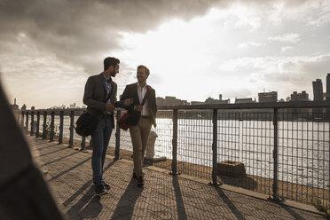 USA, New York City, two businessmen walking along East River - UUF08849