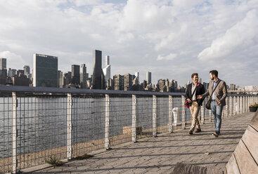 USA, New York City, two businessmen walking along East River - UUF08852