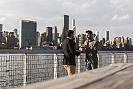 USA, New York City, two businessmen talking at East River - UUF08855