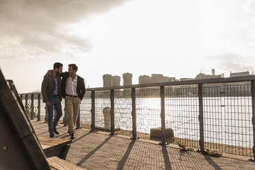 USA, New York City, two businessmen walking together along East River - UUF08858