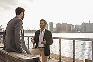 USA, New York City, two businessmen talking at East River - UUF08861