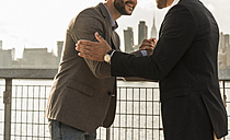 USA, New York City, two businessmen meeting at East River - UUF08867