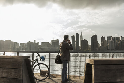 USA, New York City, businessman at East River on cell phone - UUF08873