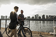 USA, New York City, two businessmen with bicycle walking along East River - UUF08876