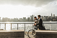 USA, New York City, two businessmen with bicycle walking along East River - UUF08882
