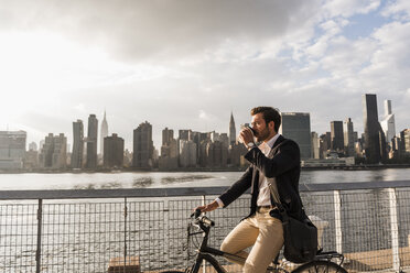 USA, New York City, businessman on bicycle with takeaway coffee - UUF08885