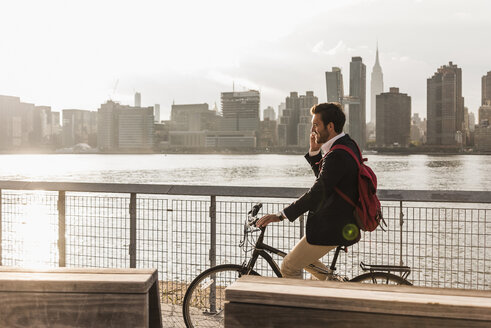 USA, New York City, businessman on bicycle talking on cell phone - UUF08888