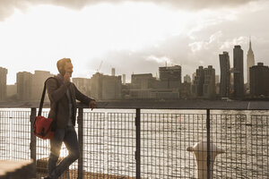 USA, New York City, businessman at East River on cell phone - UUF08891