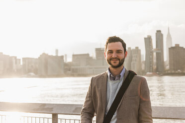 USA, New York City, portrait of confident businessman at East River - UUF08894