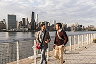 USA, New York City, two young men walking along East River - UUF08897