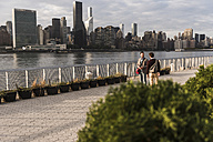 USA, New York City, two young men talking at East River - UUF08903