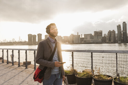 USA, New York City, young man with headphones and cell phone at East River - UUF08909