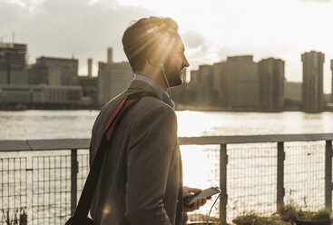 USA, New York City, young man with headphones and cell phone at East River - UUF08912