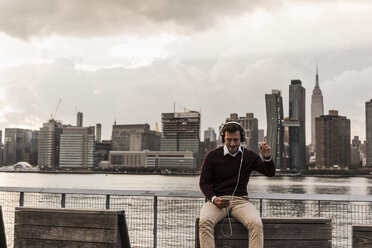 USA, New York City, young man with headphones and cell phone sitting at East River - UUF08918