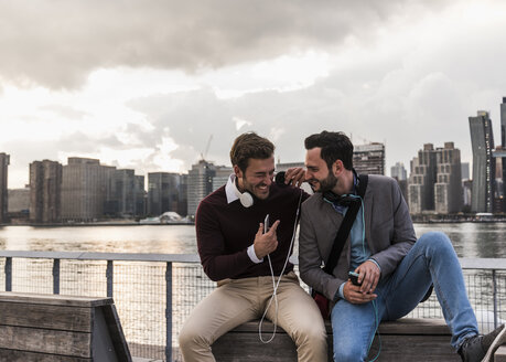 USA, New York City, two happy young men with headphones and cell phone sitting at East River - UUF08921
