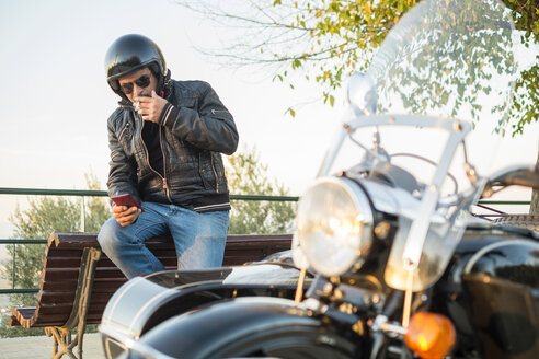 Biker wearing helmet and sunglasses having a cigarette rest looking at smartphone - JASF01269